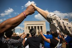 BALTIMORE, MD - MAY 03: People hold hands during a rally lead by faith leaders in front of city hall calling for justice in response to the death of Freddie Gray on May 3, 2015 in Baltimore, Maryland. Gray later died in custody; the Maryland state attorney announced on Friday that charges would be brought against the six police officers who arrested Gray. (Photo by Andrew Burton/Getty Images)