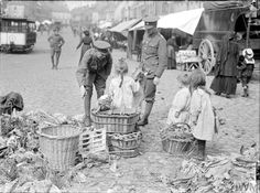 WWI, 12 Sept 1917; British soldiers buying food from children in the market-place at Cassel. © IWM (Q 2880)