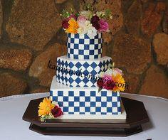 Blue checker board wedding cake with fresh flowers.