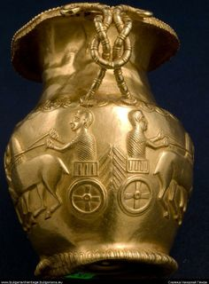The jug from the Mogilanovo's mound is 9 cm high, weighs 240 grams and is made of gold. It dates back to the third quarter of IV c. B.C. The fretwork handle has the form of a Hercules's knot.  Four unicorns are harnessed in the chariots and their bellies form a straight line. The horses' head and breast bands are decorated with round applications. In every chariot there is a charioteer - the God Apollonius.