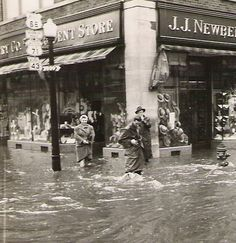 "This photo was taken during the ""Big Flood"" sometime during World War II and shows the corner of Main Street and 5th. Street in Joplin and shows the  J.J. Newberry 5 10 25 Cent Store.    Note the road signs on the lamp post,  MISSOURI US 66, MISSOURI US 71  and MISSOURI (State Road) 43."