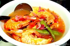 This prawn soup dish is called Sinigang, a savory-sour soup starring these luscious and plump tiger prawns. The broth/soup is flavored with sour tamarind juice, is also infused with tomatoes, red onions, ginger, and long green chilies, and finished with fish sauce to add some salty Asian depth into the broth.