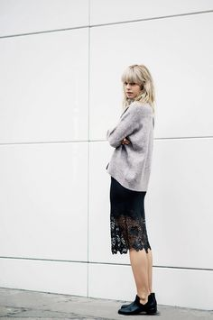 Lisa Dengler of Just Another Fashion Blog wears a gray sweater, lace-trimmed slip dress, and ankle booties