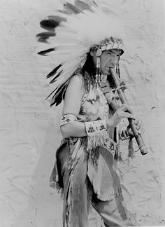 Ojibwa performer playing flute, 1937 by Marquette University Archives, via Flickr