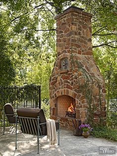 This lofty fireplace set in an outlying area lures folks out into the landscape. Appearing as if it could be equally at home in a fairy-tale forest, its rustic stonework and sculpted form enchant the eye. Vertically set stones and horizontal ledges spotlight a display niche and the arched firebox opening.