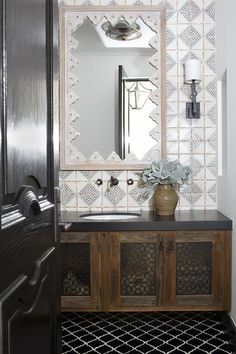 A black door complemented with a satin nickel handle opens to a Moroccan bathroom boasting black arabesque floor tiles contrasted with white grout and leading to a floating wood washstand fitted with ornate cabinet doors and a black quartz countertop.