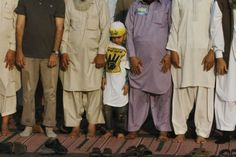 Nov. 24, 2013. A boy stands between supporters of Pakistani religious party Jamaat-e-Islami (JI) and the Pakistan Tehreek-e-Insaf (PTI) political party of former cricket star Imran Khan, as they perform evening prayers during a protest against NATO supply lines in Karachi.
