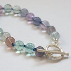 Dieses Armband wurde von mir handgeknüpft mit blauer Seidenkordel. Die Knoten kommen zwischen den Regenbogen-Fluoritperlen schön zur Geltung. Der m...