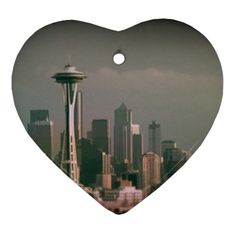 """Grey Seattle Focus Shift Heart Ornament by stineshop $13.99 Digital art, #Seattle skyline in #grey with focus shift (blurry) effect. #FiftyShades #fsog Ceramic ornaments make ideal keepsake and decorative gifts during the holiday season. Popular during the festivities such as Easter and Christmas, these accessories are also suited as in-house embellishing items. Images are imprinted onto surface using heat dye sublimation technique to prolong longevity. Measures approximately 3"""" x 3""""."""