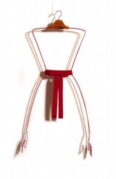 Pink Tie | 2005 | Coat hanger, copper wire, ribbon, girdle | 61 x 119 x 12.5 cm | A pair of hands extended from the neck of a coat hanger outlines the silhouette of a dress.  The dress is completed with a belt, which engulfs its own creator, the hands.