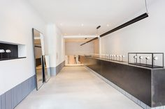 Clad in blackened steel, this counter extends the length of its store. Where the floor level steps down towards the back, the display case continues as a cantilevered element.