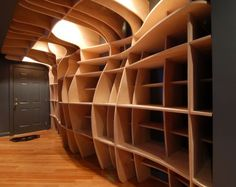 Digitally Fabricated Bookshelf by dbd Studio - An organic curving surface was created in Rhino that stretched from floor to ceiling and overhead, terminating at the existing bulkhead. 17 sheets of 3/4″ birch plywood were then CNC milled to notch together and form the undulating, gridded mass.
