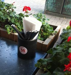 Simple table idea: take one used tin can, paint it (or not), insert cutlery and napkins, and add a table number.