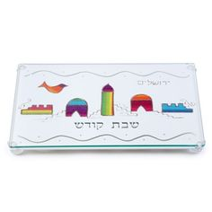 This wonderfully unique stainless steel challah board features a Jerusalem decorative motif adorned with a joyfully colorful glass design. The words Shabbat Kodesh (in Hebrew) are engraved underneath. Your Sabbath and holiday meals will never be the same!