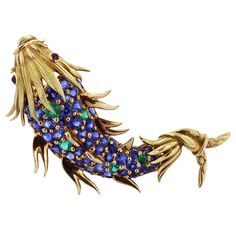 This Vintage 18 karat yellow gold fish pin is an excellent example of the elegance and charm of Schlumberger's work for Tiffany & Co. The fish consists of bead set brilliant blue sapphires and vivid green demantoid garnets with cabochon ruby eyes. The pin is stamped France, signed Tiffany & Co Schlumberger.