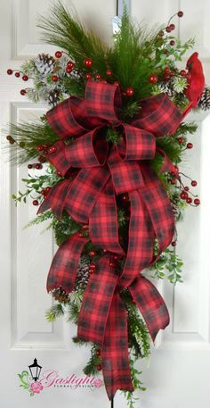 A traditional red plaid ribbon atop the Christmas teardrop swag decked in snow covered pine and cones, bountiful of red berries, long needle pine, mini eucalyptus, and winter white astilbe by Gaslight Floral Design. GaslightFloralDesign.com