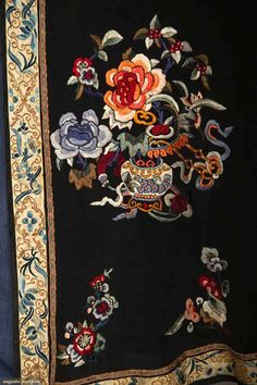 "Black silk crepe w/ floral embroidery in shades of blue & peach, narrow black sleeve band w/ blue Peking knot embroidery, wider white sleeve band w/ peach embroidery, Slv-Slv 50"", L 47"", (inner collar edge frayed, seam by side slit unstitched) very good."