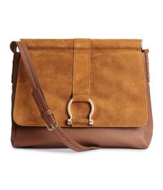 Bag in imitation leather with genuine suede details. Flap with decorative metal buckle and magnetic closure, adjustable shoulder strap, and three inner compartments, one with zip. Lined. Size 9 x 11 in.