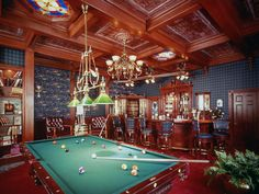 Stained-glass ceiling panels and plaid-covered walls warm the atmosphere in this Old English Pub style game room...
