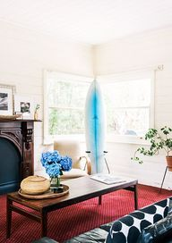 21 Homes That Prove Surf Is Chic // surfboards as decor // living room, wooden art decor fireplace mantel, black leather sofa, wooden coffee...
