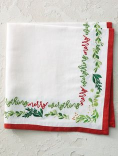"""Playful red and green embroidery that celebrates all the season has to offer. A scrolling message of """"Merry Everything"""" joins a border of printed and embroidered greenery to make any meal feel festive. Each linen/cotton napkin is trimmed in red. Holiday Wreaths, Holiday Decor, Linen Placemats, Cotton Napkins, All Things Christmas, Bag Storage, Everything, How To Memorize Things, Merry"""