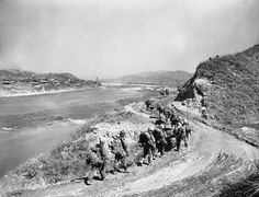 First Division Marines push northward out of Hongchon on March 16, 1951, along a winding road on the central Korean front Allied troops were being stopped by Communists holding well dug-in positions on hills northeast of Hongchon an overlooking a vital road junction. (AP Photo/Jim Pringle)