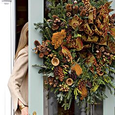 Inspired by the gold and burgundy tones of the ribbon, McManus embellished a Fraser fir wreath with berries, dried mushrooms, monkeypods, and different shades of brown pinecones dipped in wax for a lush new look.