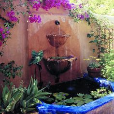 Against a rustic stucco wall, water trickles out of scalloped bowls into a colorful blue fountain bedecked with blazing bougainvillea. Although it seems like a scene from a remote Mexican village, this townhouse garden is actually located a Mexican Courtyard, Mexican Garden, Spanish Garden, Mexican Hacienda, Hacienda Style, Front Courtyard, Dream Garden, Garden Art, Garden Design