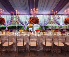 A gray and white floral tablecloth is topped with blooms and lit with candelabras and chandeliers.