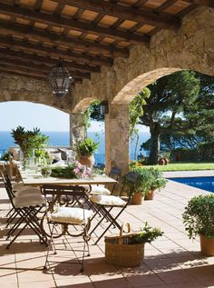 beautiful outdoor living on the water. love the simple dining table, great wood ceiling & limestone walls...feels french <3