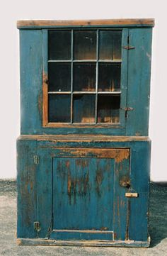 19th c. country pine stepback cupboard, in original blue painted finish, nine-panel glazed door above, inset panel door at the base.