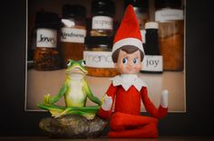 """Our funny little elf on the shelf <3 DAY 7: Jingle's Zen -- It appears Jingle was doing some meditating last night! We found him this morning, on the computer desk, sitting in front of Mom's """"Recipe For Peace"""" photo she took. OHMMM... (Look for Jingle - The Elf On Our Shelf on Facebook!) Funny elf on the shelf; Elf on the shelf ideas; Easy elf on the shelf idea"""