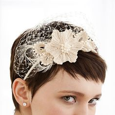 Trade a traditional veil for a more minimal accessory with this gorgeous headpiece. Pearls, feathers and veiling accent starched crochet flowers for an effect that's truly heirloom-worthy.