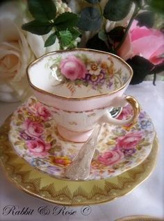 pretty tea cup, saucer and plate with rose decoration and gold trim