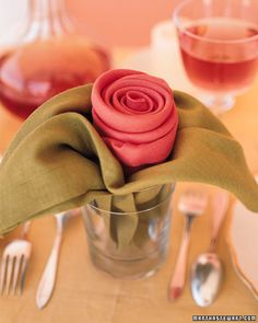 """When you imagine a romantic dinner for two, crumbs never sully your partner's face. Give your fantasy a practical twist with napkins folded into a rose-inspired arrangement. The """"flower"""" and """"leaves"""" are tucked into a tumbler and set at each place setting. Don't worry about making the corners meet perfectly -- a little unevenness looks more natural."""