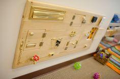 Lock board. Lose the letter box and add barrel lock, light switch, sensory under doors (fur or sandpaper), door knob with turn lock.