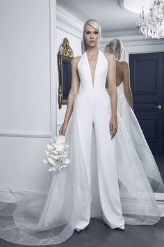 Style RK8481, pearl stretch-crepe jumpsuit featuring a deep V-halter bodice and shown with detachable transparent overskirt, [Romona Keveza](https://www.brides.com/photo/wedding-dresses/designer/romona-keveza)