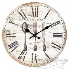Zegar Belldeco z motywem sztućów czyli okrągły zegar kuchenny z MDFu o jasnej, pokrytej przetarciami tarczy.