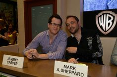 SUPERNATURAL executive producer Jeremy Carver (left) and star Mark A. Sheppard pause for a moment between signing for fans at the Warner Bros. booth at Comic-Con 2012 (© WBEI. All Rights Reserved.)