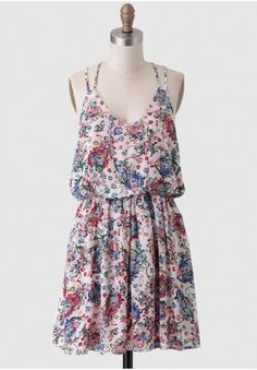 We adore this darling cream-colored frock that features an intricate floral print in hues of blue, pink, green, yellow, and red with dual skinny shoulder straps. Perfected with a racerback design...