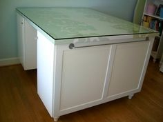 IKEA Hackers: Spring Chick's to-die-for craft room - counter height craft/sewing table made from Ikea cabinets, an mdf counter top covered with shower curtain fabric and glass! beautiful, functional and lots of storage!