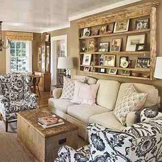 like the use of the wall space behind the couch. I really like the idea of light stained wood shelf for pictures, the molding sets it off.