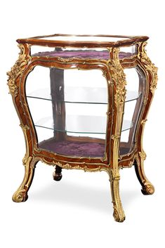 This stunning French vitrine is crafted in the opulent Louis XV style. The well-proportioned bombe form brings together tulipwood, ormolu mounts and glass panels. The table displays all of the elegance and inventiveness of this highly coveted style ~ 19th Century, France, Antique Furniture ~ M.S. Rau Antiques