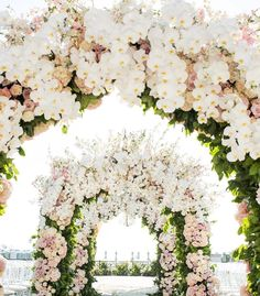 There's nothing quite like a series of #floral arches and this robust design draped in pastel blooms and lush, white orchids takes top honours! | Photography By: White Lilac Inc. | WedLuxe Magazine | #luxury #wedding #luxurywedding #weddinginspiration #floralarch #floraldesign #design #decor