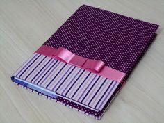 Caderno pequeno brochura 96 folhas com capa removível em cartonagem com duas cores de tecido 100% algodão e fita de cetim.    Esta capa também comporta cadernos em espiral (valor diferenciado para este tipo de caderno). R$ 40,95