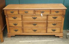 BEAUTIFUL WOOD CHEST OF DRAWERS OR BUREAU BY YOUNG REPUBLIC INDIANA. BUREAU MEASURES 59 INCHES IN LENGTH, 19 INCHES DEEP AND 34 INCHES TALL. IT HAS 11 DRAWERS WITH METAL HARDWARE AND CARVED ACORN ACCENTS. SHOWS SOME SIGNS OF WEAR.