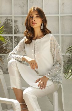 The perfect party dress. This classic white salwar kameez is detailed with silver tilla and mirror work along the sleeves. Crystal buttons and silver edging along every seam of the tunic add the finis Simple Pakistani Dresses, Pakistani Dress Design, Simple Dresses, Stylish Dresses, Casual Dresses, Pakistani White Dress, Girls Dresses, Pakistani Fashion Party Wear, Pakistani Wedding Outfits