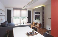Zajímavým prvkem v obývací části jsou dva vysoké radiátory umístěné symetricky vedle francouzského okna. Barevně navazují na antracitovou dlažbu v kuchyni a tmavou sedací soupravu