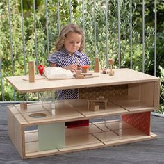 The QUBIS HAUS by Amy Whitworth is a coffee table that transforms into a dolls house with the simple addition of sliding panels made from wood and perspex, enabling the 'designer' to create different room layouts.