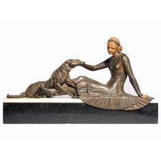 This Leduc, Art Deco collectible piece of a lady with a dog is carved in bronze. The lady's intricate face is made of bone and alabaster, and the figures sit on a marble base. Circa 1920.  Available on Artisera